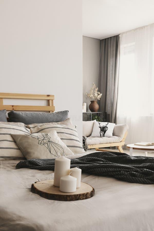 Свечи на деревянном подносе хобота на реальном фото яркой спальни открытого пространства внутренней с окном с задрапировывают стоковые фотографии rf