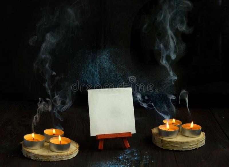 Свечи на старой деревянной предпосылке с дымом и мольбертом стоковые фотографии rf