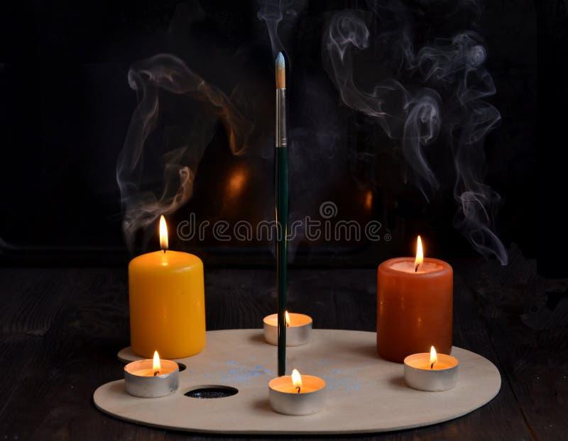 Свечи на старой деревянной предпосылке с дымом и щеткой стоковые фото