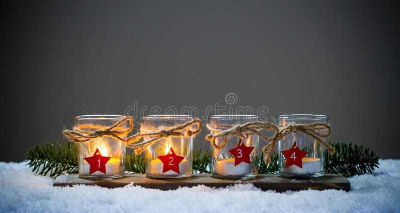 4 свечи пришествия в снеге стоковое фото