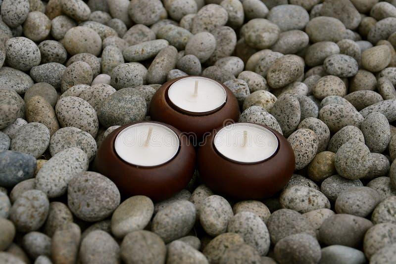3 свечи сидя на камешках стоковое фото