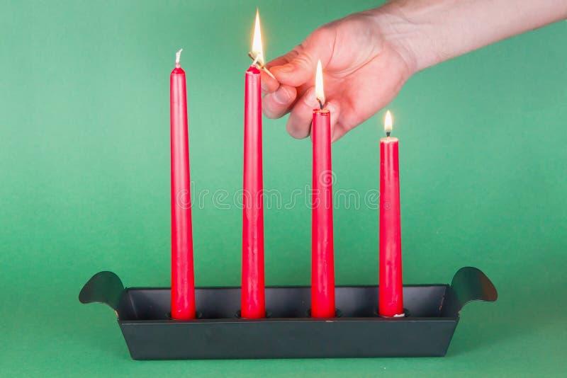 свечки пришествия осветили треть красного цвета стоковое изображение
