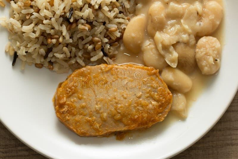 Свиная отбивная, рис Брайна и белые фасоли Белое блюдо на деревянном tabl стоковые фото