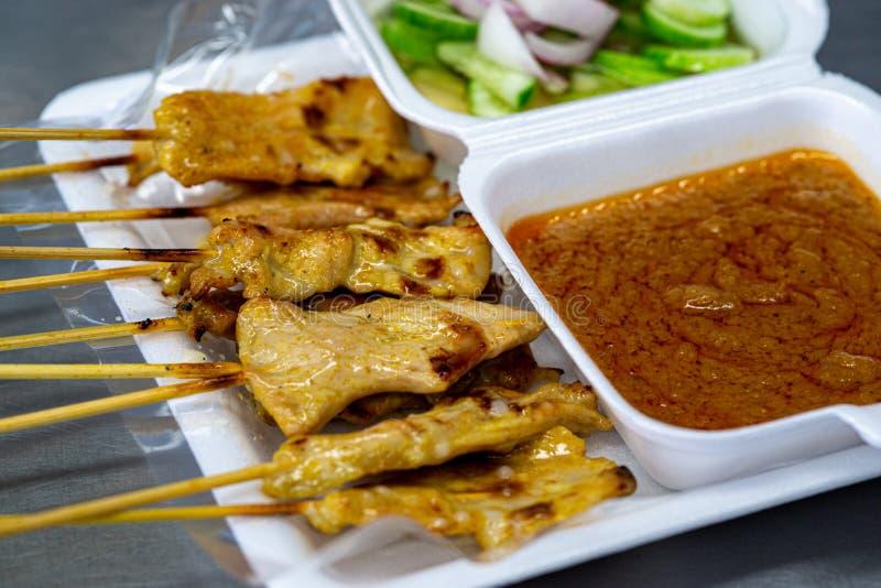 Свинина satay, тайская еда улицы зажарила свинину, который служат с соусом арахиса и кислым соусом стоковое изображение