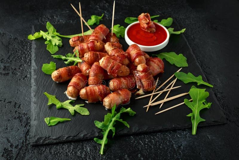 Свиньи еды пальца партии в одеялах на зубочистках с соусом кетчуп и дикими листьями ракеты стоковое изображение rf