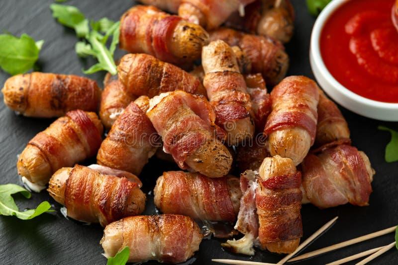 Свиньи еды пальца партии в одеялах на зубочистках с соусом кетчуп и дикими листьями ракеты стоковое изображение