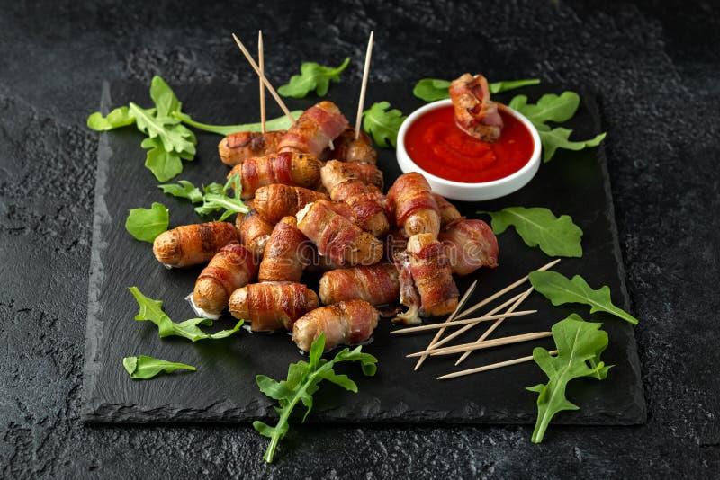 Свиньи еды пальца партии в одеялах на зубочистках с соусом кетчуп и дикими листьями ракеты стоковое фото