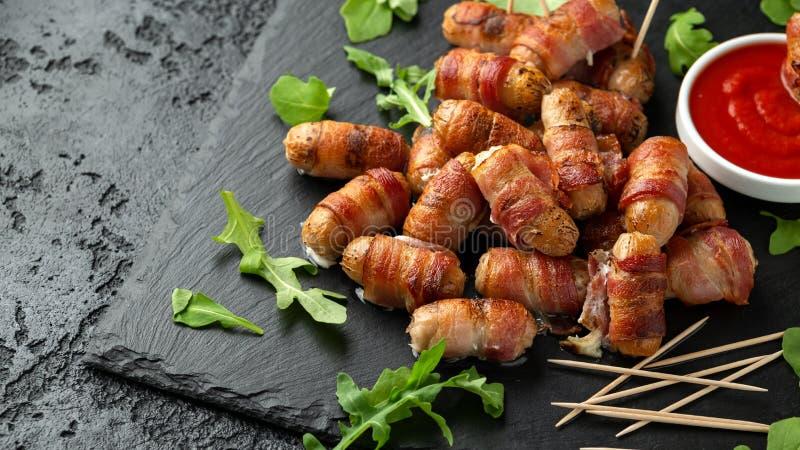 Свиньи еды пальца партии в одеялах на зубочистках с соусом кетчуп и дикими листьями ракеты стоковая фотография rf