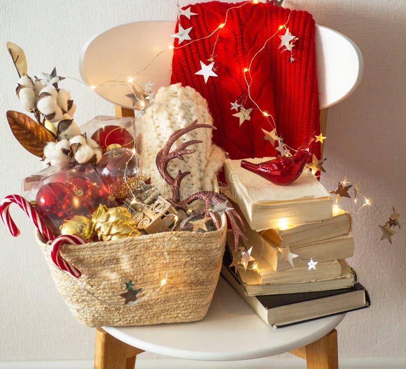 2 свитера зимы положенного на стул с корзиной украшений рождества, книг, светов приведенных строки Чтение зимы Настроение зимы стоковая фотография rf