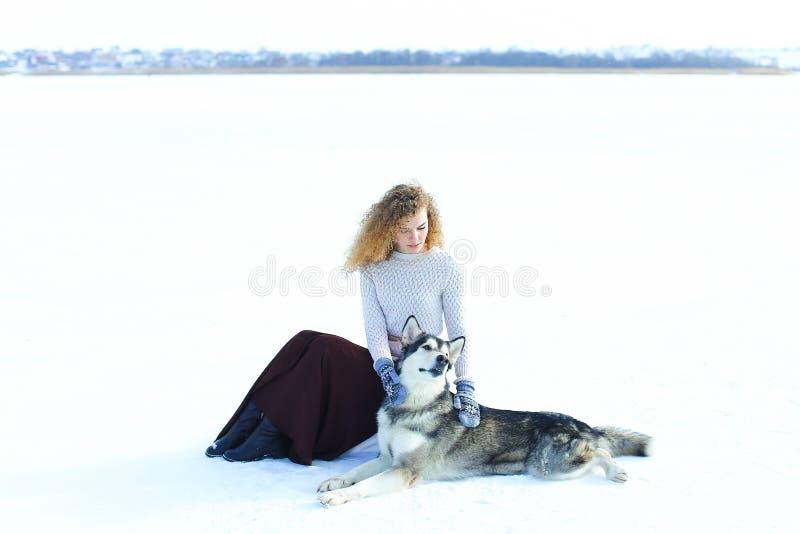 Свитер девушки нося, коричневая юбка и mittens сидя на снеге и обнимая лайку собаки стоковые изображения