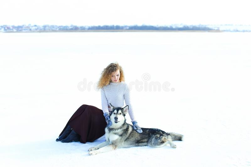 Свитер кавказской девушки нося, коричневая юбка и mittens сидя на снеге и обнимая лайку собаки стоковое изображение