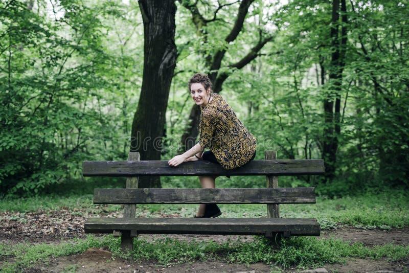Свитер молодой женщины нося и представлять деревянной скамьей в p стоковые изображения rf