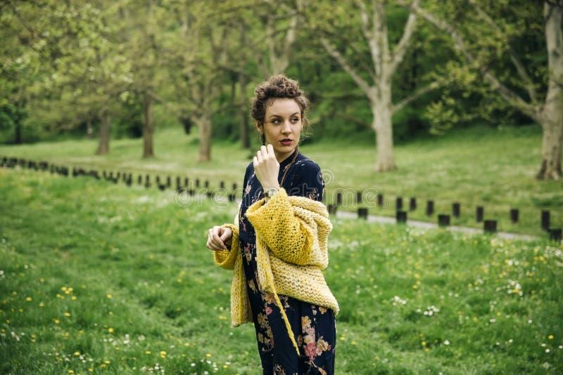 Свитер молодой женщины нося и представлять парк стоковое изображение rf