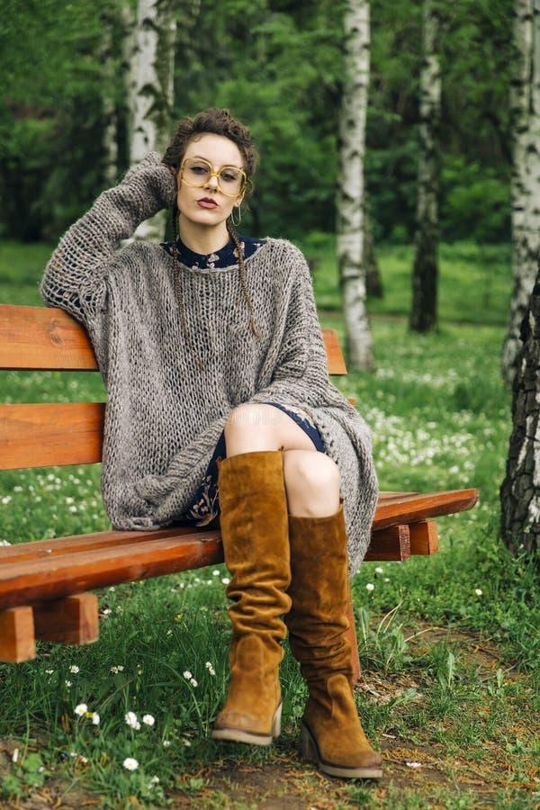 Свитер молодой женщины нося и сидеть на деревянной скамье в стоковое изображение rf