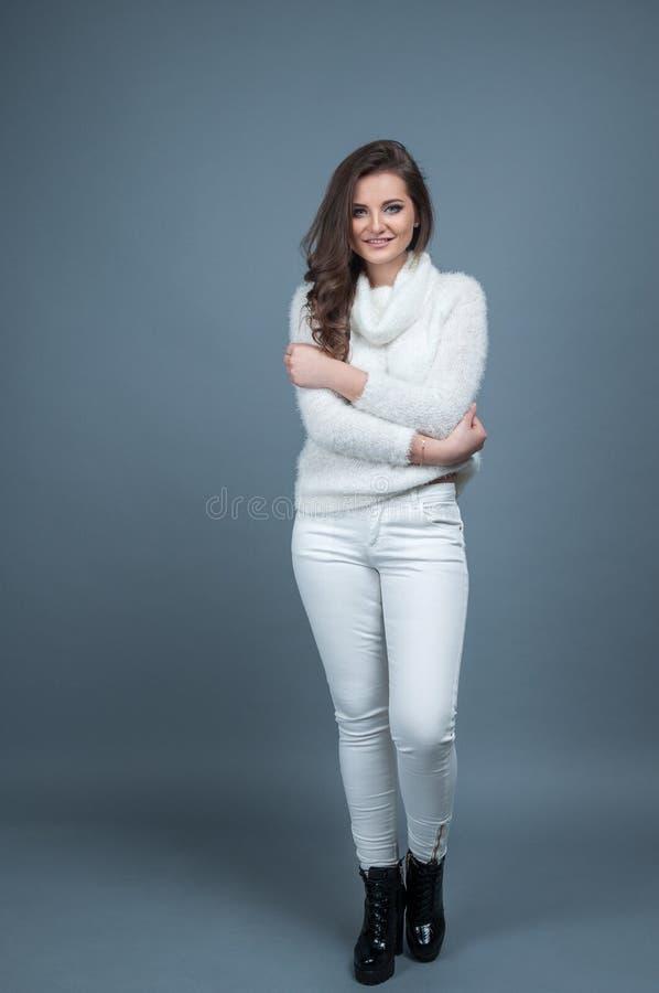 Свитер улыбки и носить девушки портрета молодой красивый связанный белый, изолированный на серой предпосылке стоковая фотография