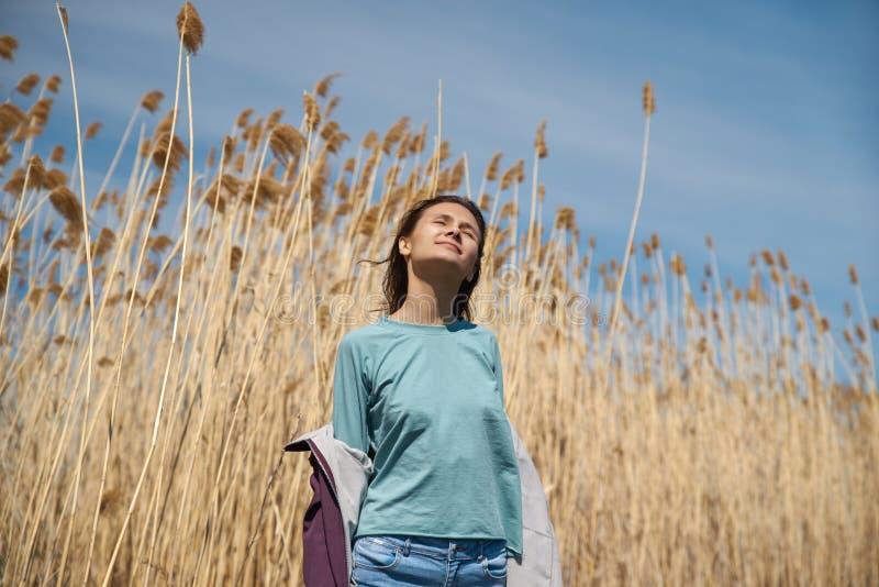 Свобода, концепция душевного спокойствия Красивая молодая женщина идя в золотое пшеничное поле с пасмурной предпосылкой голубого  стоковое фото rf