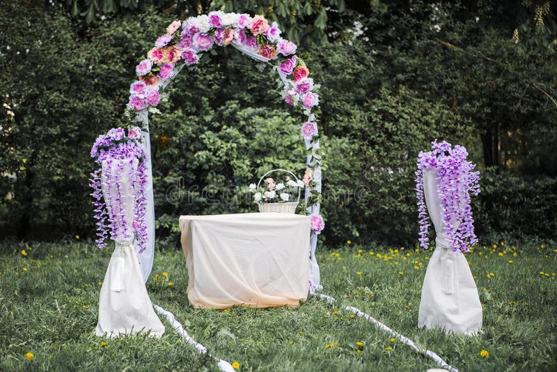 Свод свадьбы с pirple и розовые цветки на траве стоковые фотографии rf