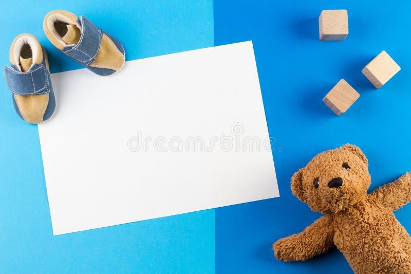 Свой мальчик, голубая предпосылка детского душа темы или питомника с пустой карточкой, besr игрушечного, деревянные блоки и ботин стоковые изображения