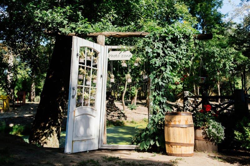 Свод свадьбы при белая дверь перерастанная с плющом стоковые фотографии rf