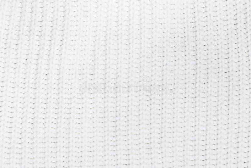 Свяжите предпосылку текстуры белыми ткани связанной шерстями стоковая фотография