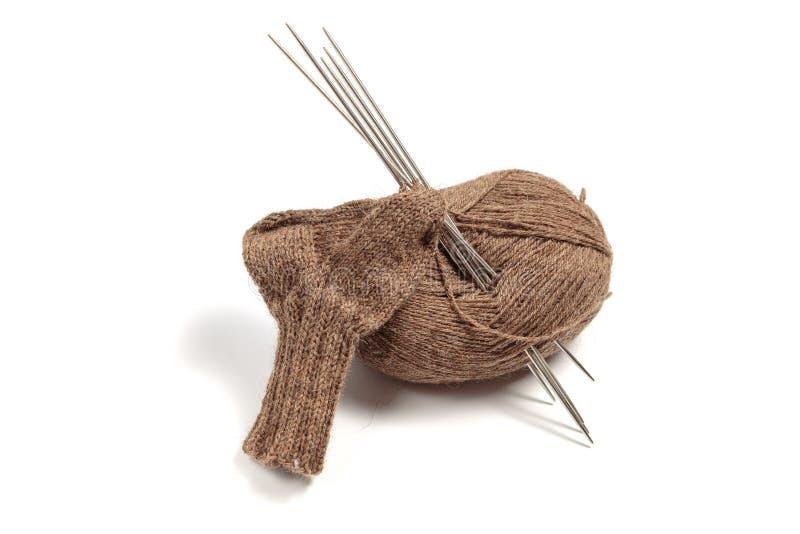 Связанные носки и коричневое пасмо пряжи с иглами на белой предпосылке стоковая фотография rf