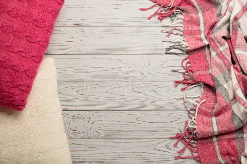 Связанные подушки и шотландка на светлой деревянной предпосылке стоковые изображения