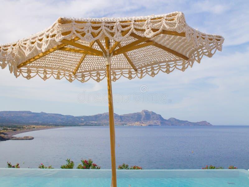 Связанный зонтик пляжа около бассейна с морем и горным видом стоковое изображение rf