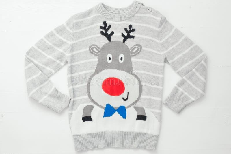 Связанный свитер с смешными оленями рождества на деревянной белой предпосылке Уродский свитер стоковые фото