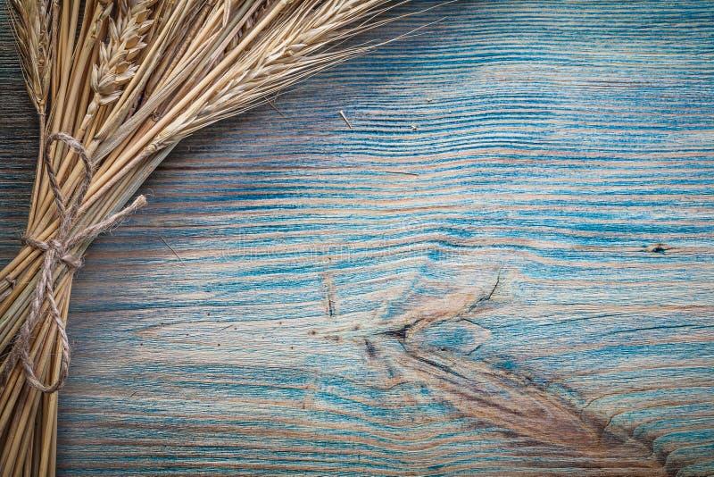 Связыванный пук золотых ушей рож пшеницы на винтажном деревянном экземпляре доски стоковое фото rf