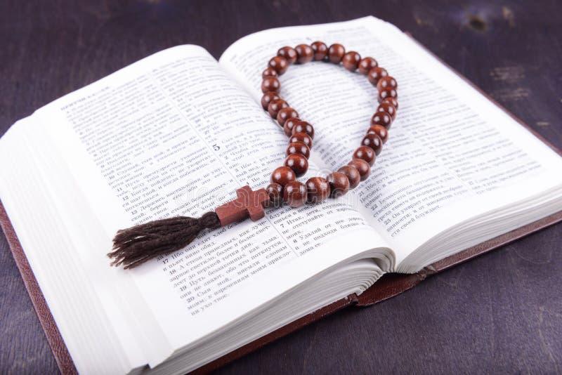 Святая книга и крест на деревянной предпосылке стоковые фото