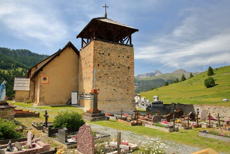 Святой Romain церков en Queyras Molines деревушки, с усыпальницами на переднем плане и горный пик Rochebrune в backgro стоковое изображение rf
