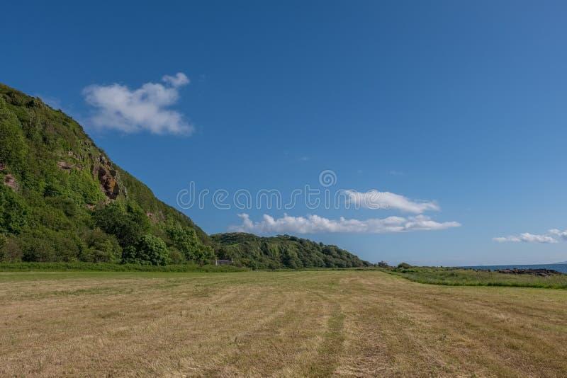Святые пещеры или Hawking пещера Craig расположенные над земным Leval в Portencross на летнем солнцестоянии в Шотландии стоковые изображения
