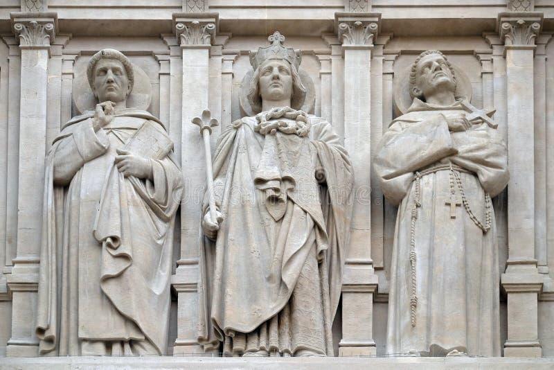 Святые Dominic, Луис и Фрэнсис Assisi, статуя на фасаде церков Августина Блаженного в Париже стоковое фото rf