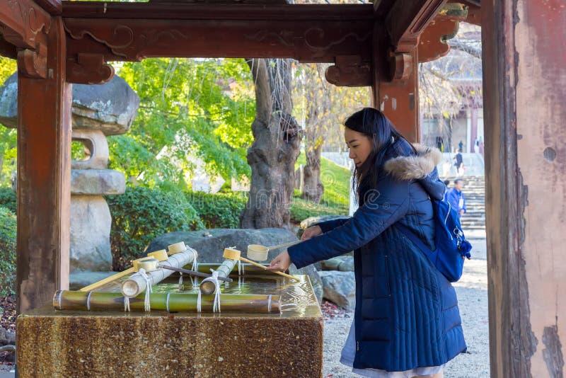 Святыня святой воды при туристы черпая воду стоковое изображение rf