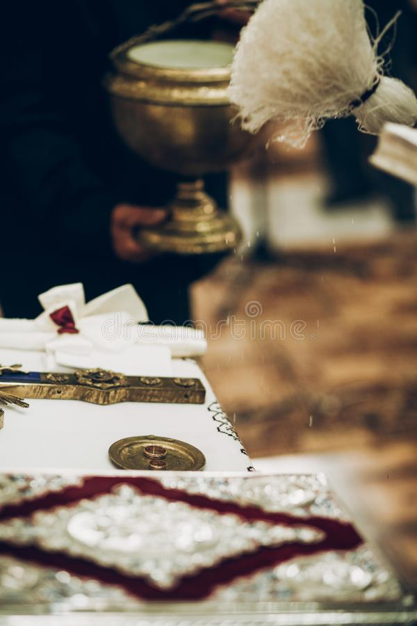 Священник благословляя золотые обручальные кольца на алтаре в церков во время w стоковые фотографии rf