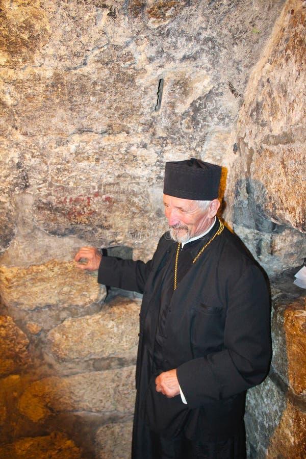 Священник в церков St Лазаря, усыпальнице Лазаря, расположенной в городке западного берега al-Eizariya, Bethany, около Иерусалима стоковые фото