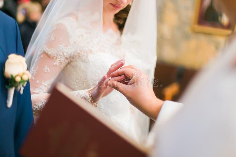 Священник кладет кольцо на палец невесты во время свадебной церемонии стоковые фото