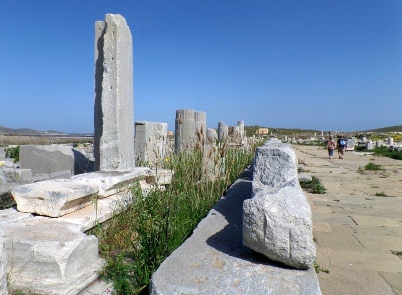 Священный путь с старыми руинами в археологических раскопках Delos, месте всемирного наследия ЮНЕСКО на острове Delos стоковая фотография rf