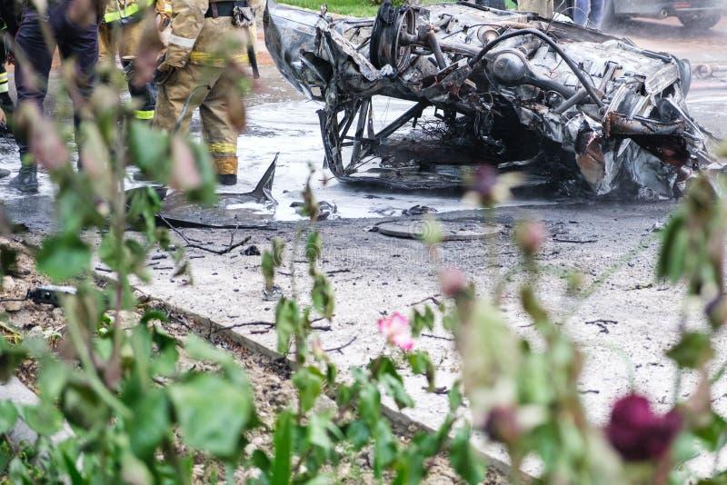 Сгорели автомобиль после аварии на дороге Пожарные стоя рядом Изображение репортажа стоковое фото rf