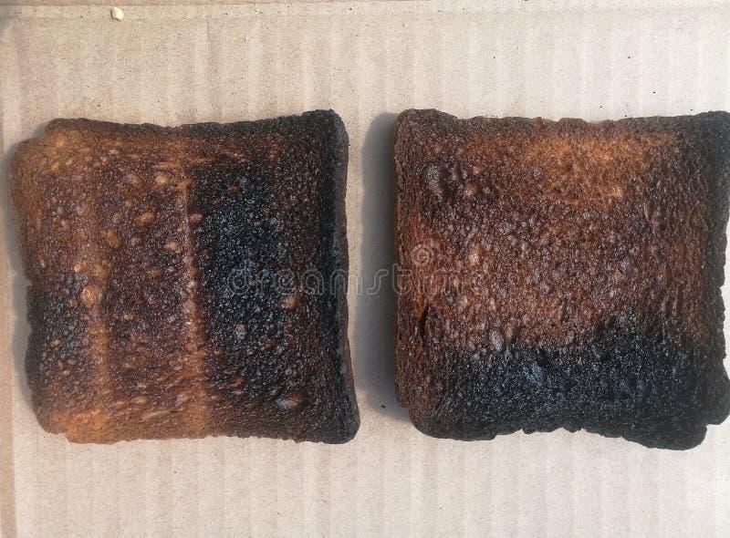сгорели хлеб тоста, куски палил хлеб на бумажной стене стоковая фотография rf