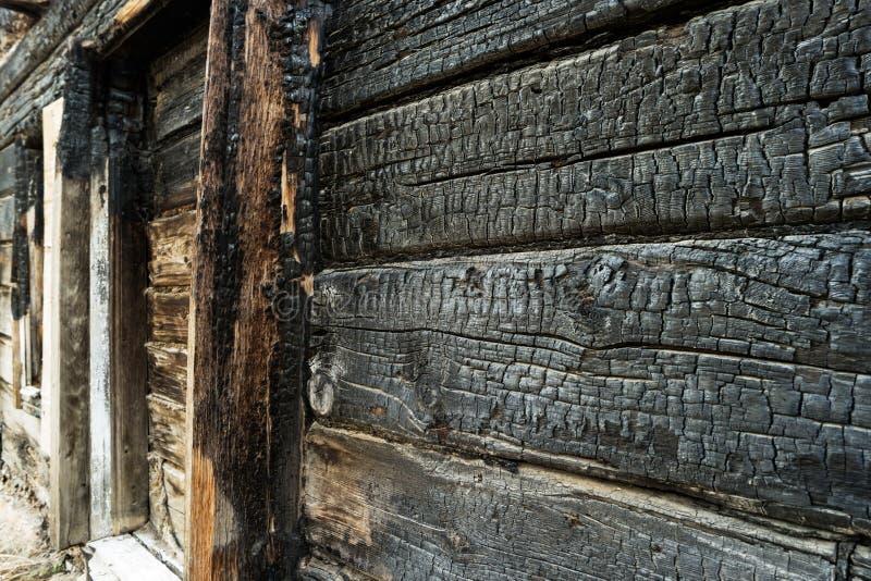 Сгоренная черная деревянная стена Двиньте под углом изображение, который сгорели доски дома трущобы стоковое фото rf