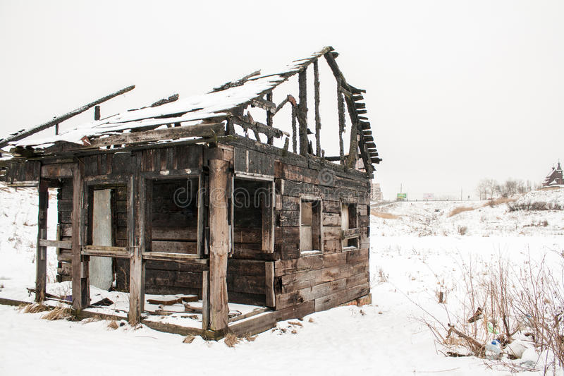 Сгорели деревянный дом на белом снеге стоковые фото