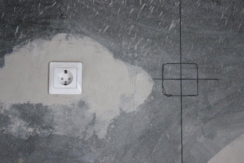 Сделайте плиты стены для переключателей и штепсельные розетки в бетонной стене ремонт в квартире или доме Строительство повторная стоковая фотография rf