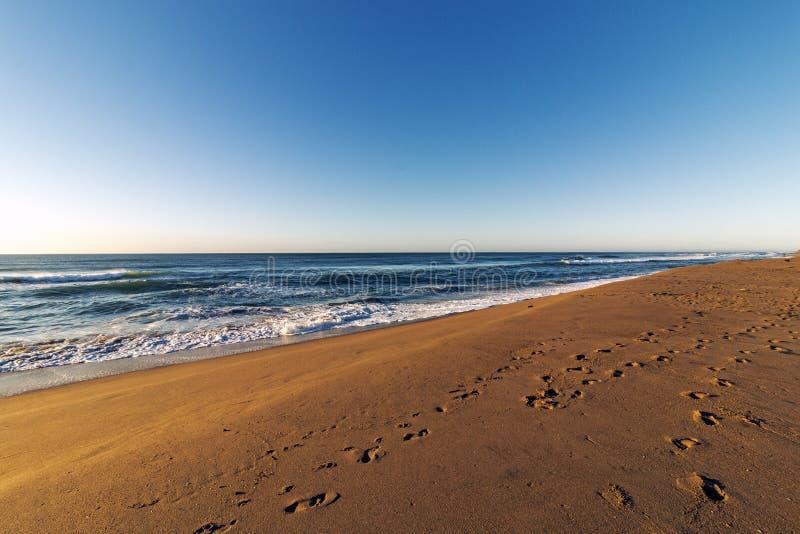 Сделанный по образцу песок пляжа с ландшафтом голубого неба следов ноги прибрежным стоковая фотография