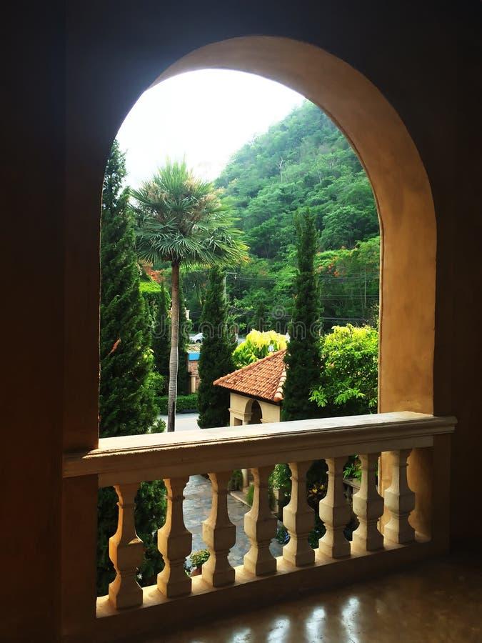 Сдобренные оконные рамы сделали конкретного, кривая рамки окна под открытым небом с перилами балкона для того чтобы наблюдать взг стоковое фото rf