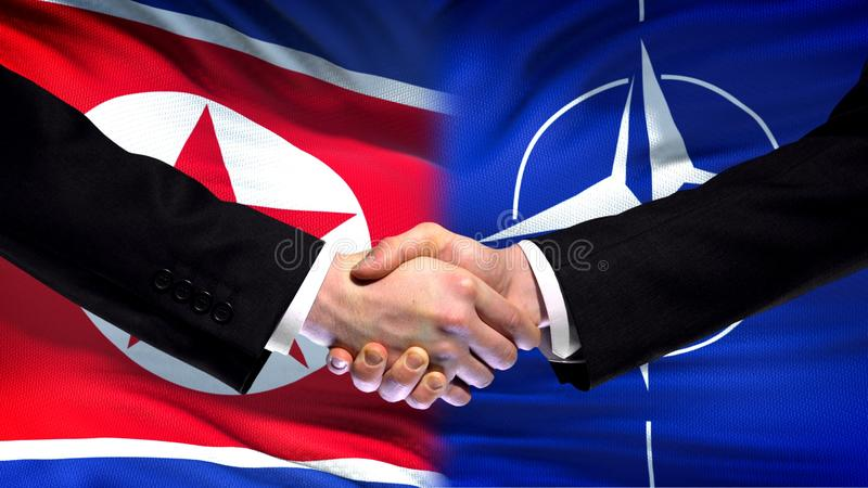 Северная Корея и рукопожатие НАТО, международное приятельство, предпосылка флага стоковое изображение rf