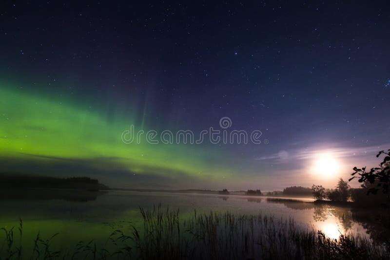 Северное сияние и полнолуние над озером в Финляндии стоковые изображения rf