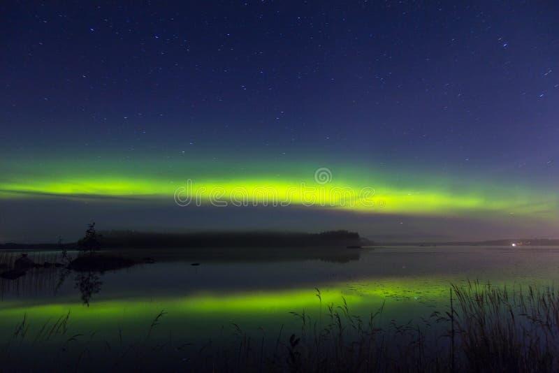 Северное сияние над озером в Финляндии стоковые фото