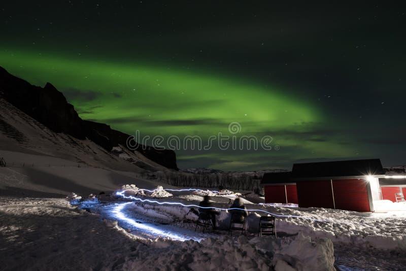 Северные сияния внутри с световыми эффектами, людьми визируют видеть света рассвета в Исландии стоковая фотография