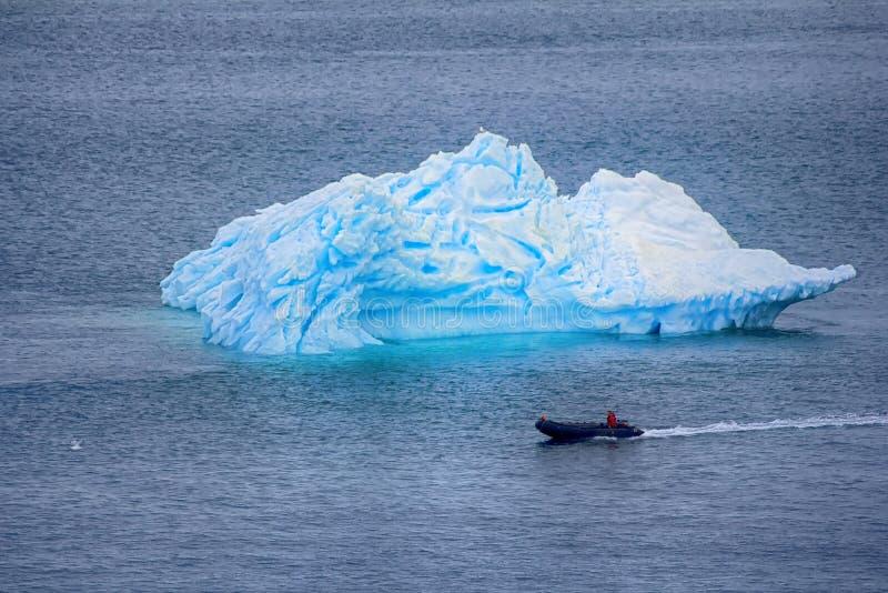 Северный океан, айсберг и приполюсный человек на моторке стоковое фото rf